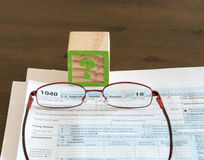 Tax preparation problems for IRS form. Question mark wooden block illustrating problems or issues in completing US IRS tax form stock photos