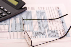 Tax preparation supplies, reading glasses and tax forms. Tax preparation supplies, reading glasses and blank tax forms stock photo
