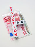 Tax reduction Euro area. Text ' reduction ' and ' tax '  inscribed on small cubes and arranged crossword style with common letter ' t ' on Euro notes isolated Stock Image