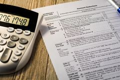 Tax reform planning concept with tax preparation forms for standard deductions. On wooden board with calculator Royalty Free Stock Photo