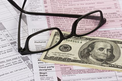Tax Refund. Cash and eyeglasses on top of a U.S. tax form with focus around refund Stock Images