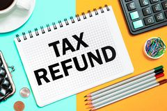TAX REFUND with the office tools on yellow blue background . Concept TAX REFUND