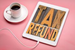 Tax refund word abstract in wood type. Tax refund - word abstract in vintage letterpress printing blocks on a digital tablet with a cup of coffee stock images