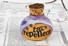 Tax repellent bottle and tax form. A bottle of corked tax repellent and eyeglasses on top of 1040 income tax form Stock Photo