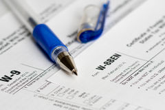 Tax reporting forms with opened blue pen stock photo