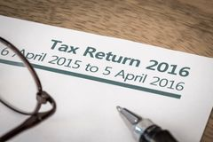 Tax return UK 2016. UK Income tax return form for 2016 on a desk with pen and glasses Stock Photos