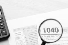 Tax returns through a magnifying glass Stock Photos