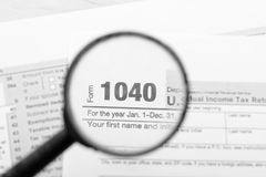 Tax returns through a magnifying glass Royalty Free Stock Image