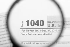 Tax returns through a magnifying glass Stock Image