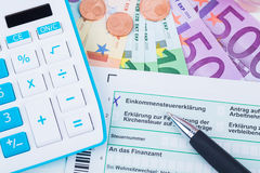 Tax revenue. Blue calculator with tax forms Royalty Free Stock Photo