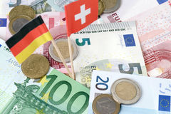 Tax sinner. Euro banknotes and swiss and germany flag Royalty Free Stock Photography