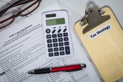 Tax Strategy still life business finance concept with calculator and tax forms royalty free stock photo
