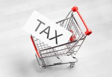 Tax, taxation and VAT concept. Shopping cart with a card or paper sign Royalty Free Stock Photo