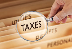 Tax Taxes File Reform Evasion Plan. Tax files being examined with a magnifying glass Stock Images