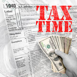 Tax Time. A tax time themed montage for US taxpayers with a hand full of money fanned out Royalty Free Stock Photography