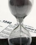Tax Time. Hour glass tight with 1040 form in background Stock Photography