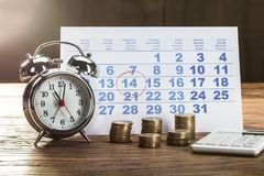 Tax Time On Alarm Clock With Coins. Calculator And Calendar Over The Wooden Table Stock Photography