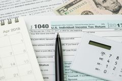 Tax time in April concept, pen on 1040 US individual income tax. Filling form with calendar and calculator stock photos