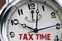 Tax time concept clock closeup isolated on white background with. Red words Stock Images