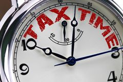 Tax time concept clock closeup isolated on white background with. Red words Royalty Free Stock Photos