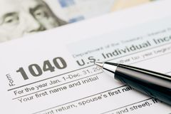 Tax time concept, selective focus on pen on 1040 US individual i. Ncome tax filling form with US dollar bill, calculate from yearly revenue to pay the government royalty free stock image
