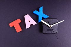 Tax time. Concept word tax and clock on isolated on dark background royalty free stock photo