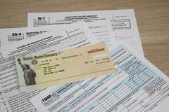 Tax Forms and Fake government check. Tax time with tax forms and sinking in debt with small social security checks or Disability Check SSI. Individual Tax Return royalty free stock photo