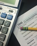 Tax Time II. Image of calculator, pencil, and IRS 1040 income tax form royalty free stock photography