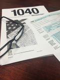 Tax Time IV. Image of glasses, 1040 income tax return filing instructions, and 1040 IRS income tax return form stock image