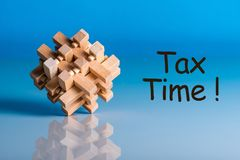 Tax time - message on blue background with wooden brain teaser Royalty Free Stock Photos