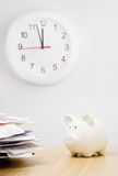 Tax time. A stack of bills next to a piggy bank with a clock behind Stock Photo