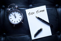 Tax Time written on paper next to alarm clock Royalty Free Stock Photo