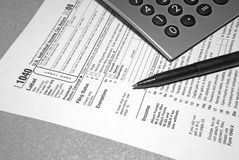 Tax Time1. Tax form in black and white with pen and calculator Royalty Free Stock Image