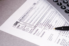 Tax Time2. Tax form with pen and calculator, Shallow DOF with focus on 1040 Stock Photo