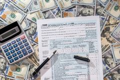 1040 tax from with us dollar banknote, pen and calculator.  stock photos