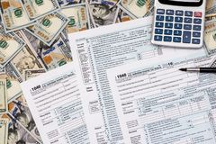 1040 tax from with us dollar banknote, pen and calculator.  royalty free stock images