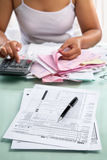 Tax from and woman calculating bills Stock Image