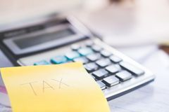 Tax word post it note and calculator, tax season concept. Background Royalty Free Stock Photo