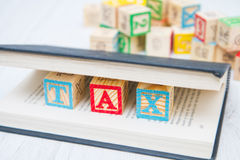 A tax written on wooden cubes Stock Image