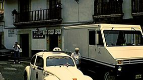 Taxco de Alarcon downtown in Mexico. Taxco De Alarcon, Mexico - Circa 1970: Taxco downtown roads, with Volkswagen beetles taxi and old cars. Archival of Mexico stock video