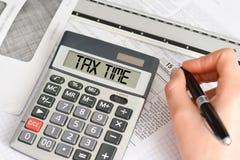 Taxe o conceito do tempo com a calculadora de mão e o formulário de imposto Fotos de Stock Royalty Free