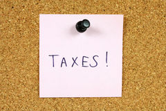 Taxes. Pink sticky note pinned to an office notice board. Taxes reminder - you need to fill your income statement Stock Photos