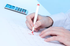 Taxes. Hand write word taxes into calendar Royalty Free Stock Photo