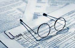 Taxes. Photo of of Eyglasses on Top of Tax Forms - Tax Related Stock Photos