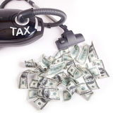 Taxes. Vacuum sucking up money in a spot light Suggest to collect taxes Royalty Free Stock Images