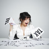Taxes. Very surprised woman at her desk looking at terrible tax bills royalty free stock photos