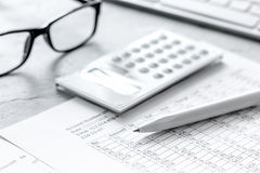 Taxes accounting with calculator in office work space on stone desk background top view. Business taxes accounting with calculator in office work space on stone Stock Image