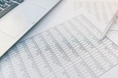 Taxes and accounting. Summary table. Pen and notebook on papers with calculations.. Taxes and accounting. Summary table. Pen and notebook on papers with stock photo
