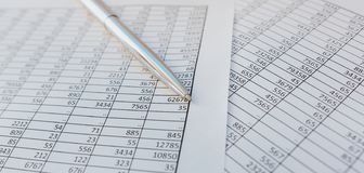 Taxes and accounting. Summary table. Pen and notebook on papers with calculations.. Taxes and accounting. Summary table. Pen and notebook on papers with stock photography