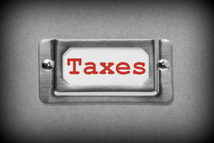 Taxes Drawer Label. A black and white image of a metal drawer label holder with a white card and the title Taxes added in red text Stock Photography